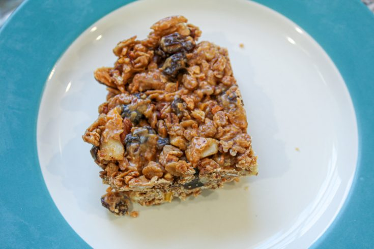 Picture of chewy homemade granola bar from above sitting on a white plate with a wide blue rim