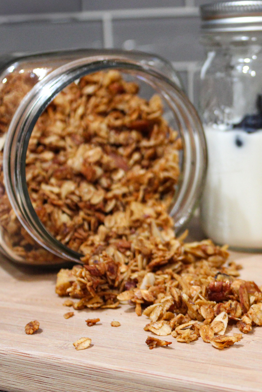 Jar of gingerbread granola spilling out onto cutting board