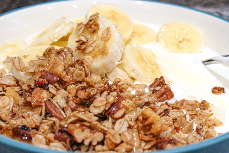 Honey nut granola in a bowl with yogurt, banana slices, and honey
