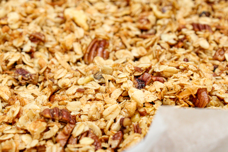 Baked honey nut granola siting on parchment paper in a glass pan