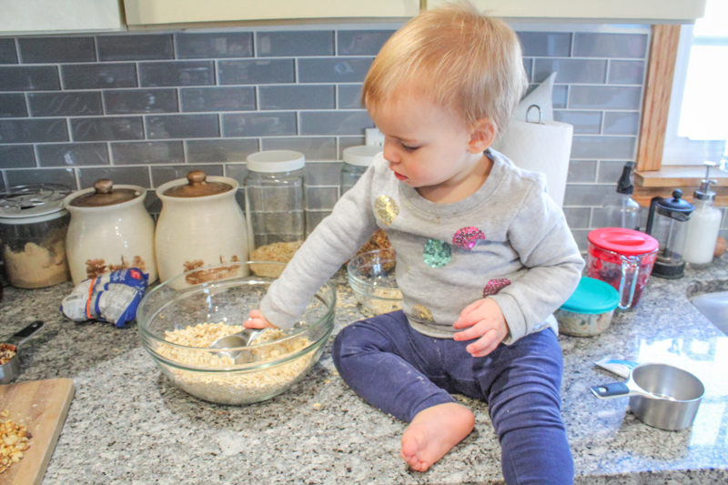Young girl sitting on counter scooping oats with a measuring cup in a glass bowl.