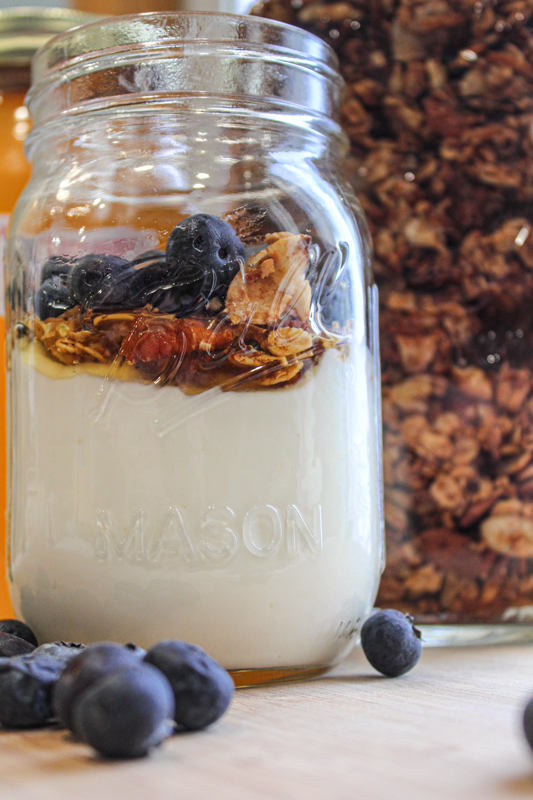 Mason jar filled with homemade yogurt topped with honey, granola, and blueberries