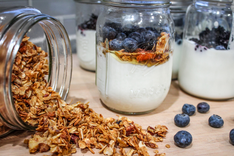 Jars of homemade instant pot yogurt topped with fruit sitting on a cutting board with blueberries and granola