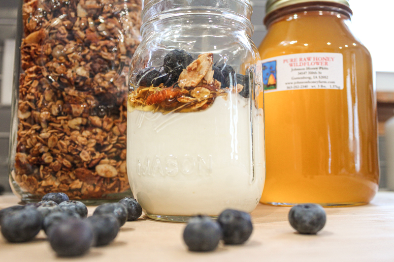 glass mason jar of homemade instant pot yogurt topped with honey, granola, and blueberries