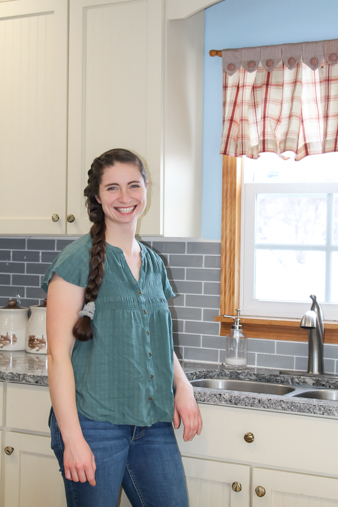 Juliana standing in front of sink in farmhouse kitchen