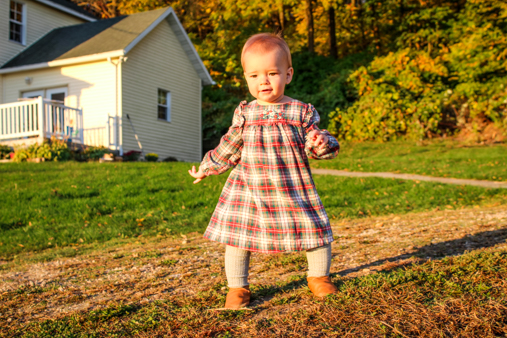 Little girl standing in front of yellow farmhouse on gravel driveway