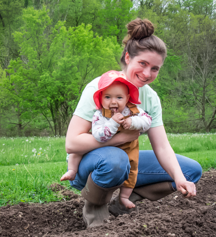 Juliana holding 6 month old daughter squatting in the garden planting seeds