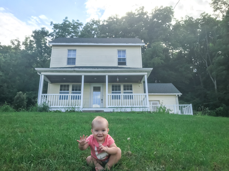 little girl in the yard in front of a 1900 farmhouse