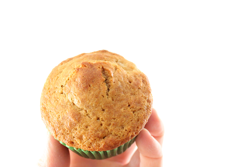Hand holding einkorn apple cinnamon muffin in front of a white wall