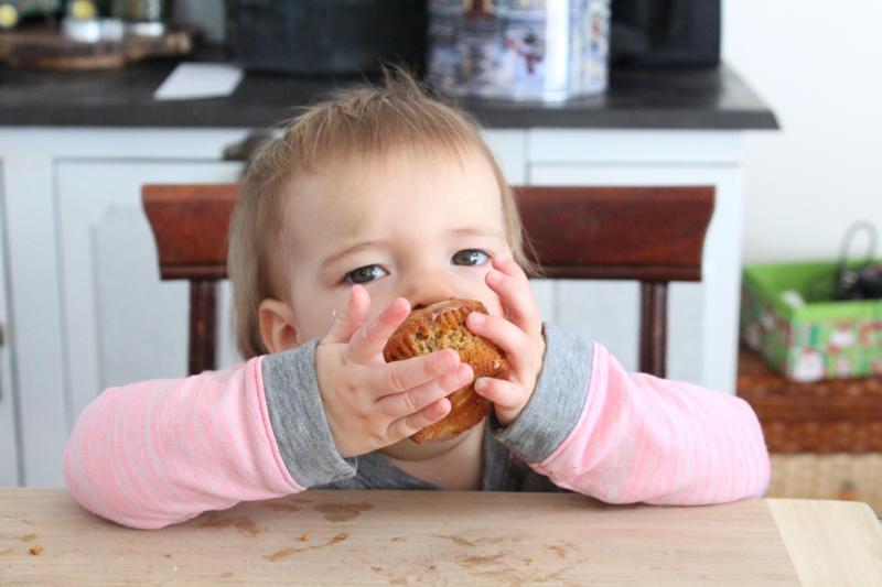 little girl eating a muffin