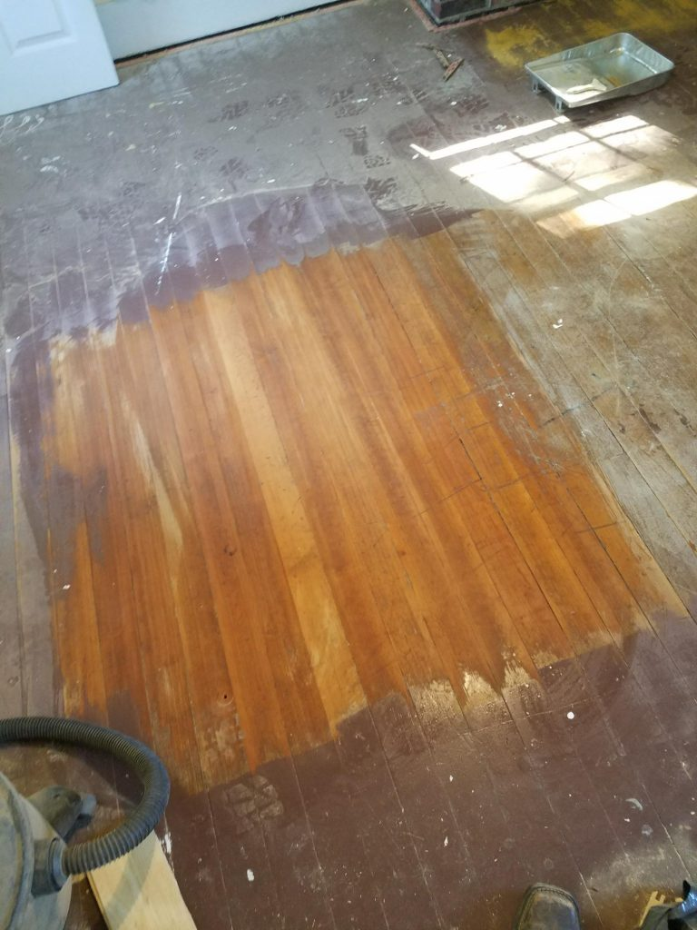 sanded patch of hardwood floor surrounded by paint in the master bedroom of the farmhouse