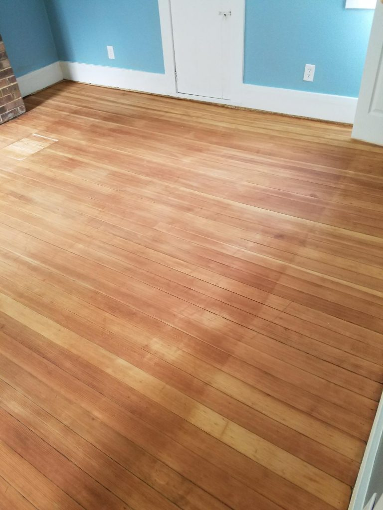 freshly sanded hardwood floor in the master bedroom of the farmhouse