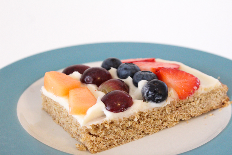 A slice of fruit pizza on a blue rimmed plate in front of a white wall