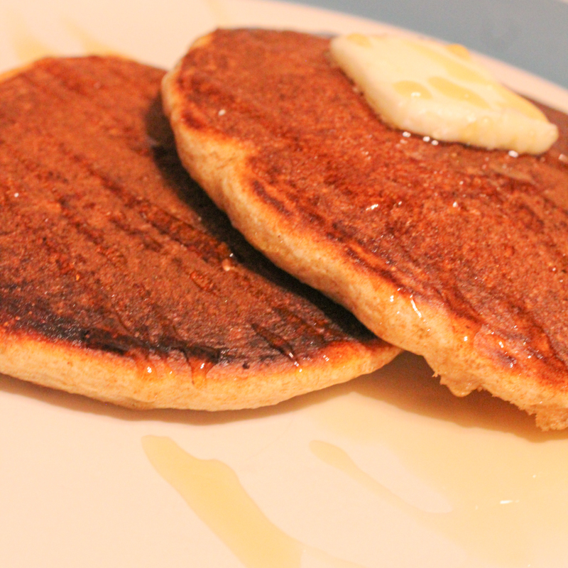 two sourdough pancakes sitting on a plate with syrup and butter
