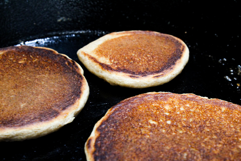 three flapjacks cooking in a cast-iron skillet.