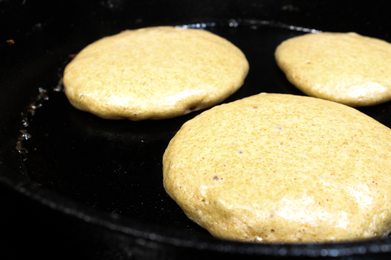 flapjack batter cooking in a cast-iron skillet