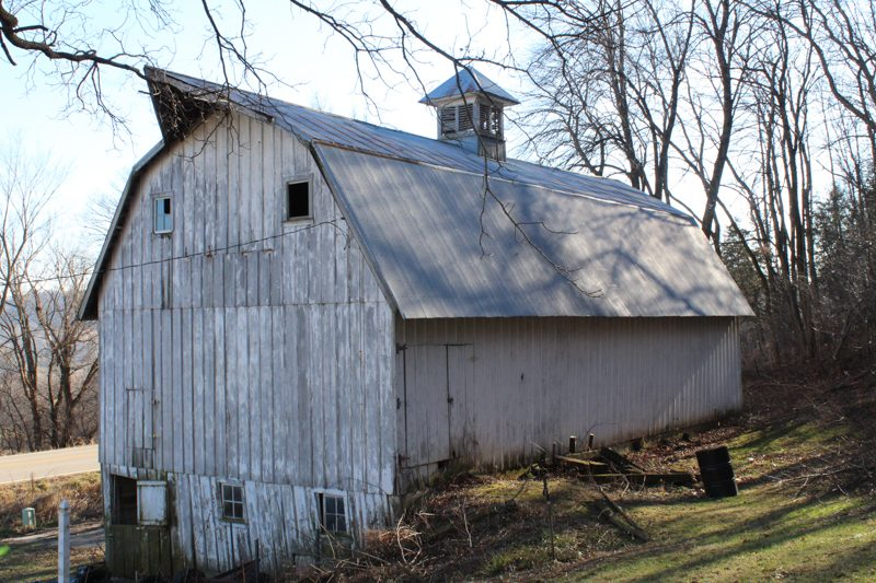 Frontal side view of a large white barn with a hayloft