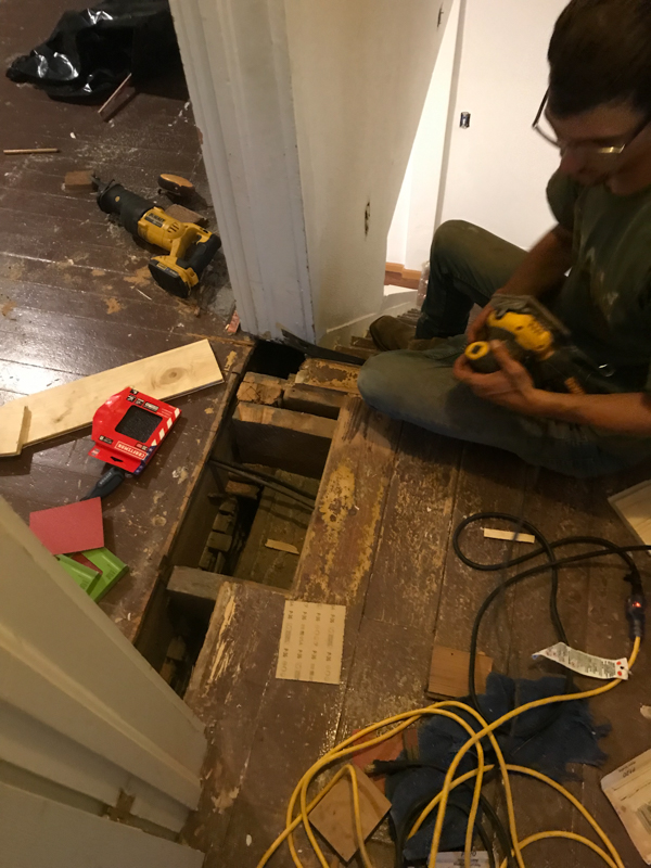 man replacing boards in the floor at the doorway of the master bedroom in a farmhouse