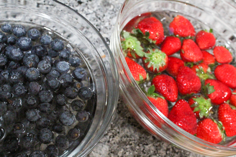 a bowl of blueberries and a bowl of strawberries soaking in water and vinegar