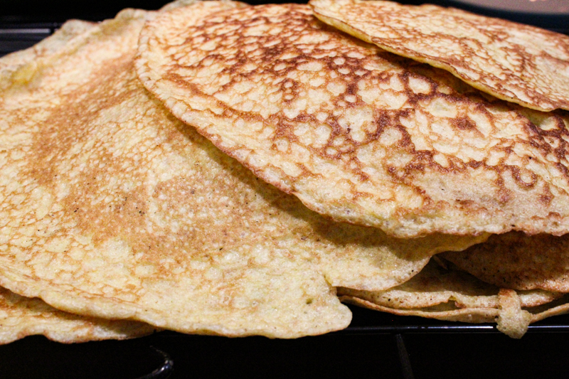 pile of sourdough crepes on a cookie sheet