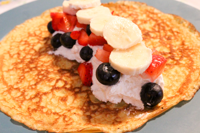 a crepe sitting flat on a plate topped with cream, blueberries, strawberries, and bananas.