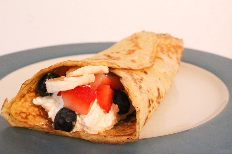 sourdough crepe rolled up on a plate filled with cream and fresh fruit
