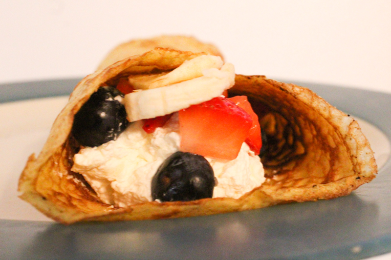 sourdough crepe filled with cream, blueberries, strawberries, and bananas.