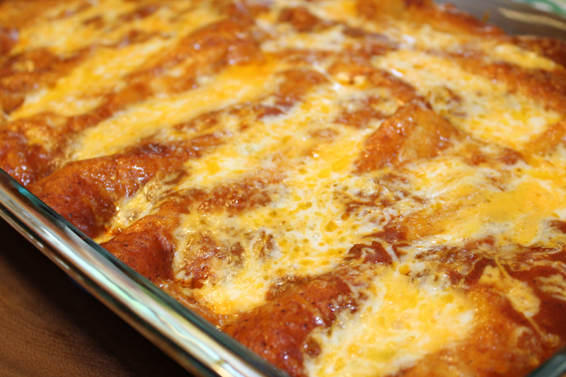 pan of baked enchiladas topped with cheese