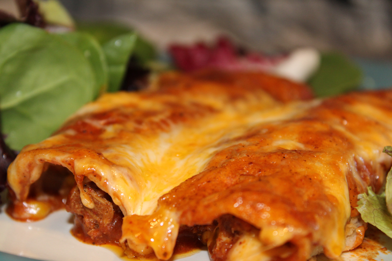 two enchiladas plated with salad