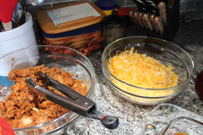 one bowl with pulled mexican pork next to a bowl of shredded cheese on the counter