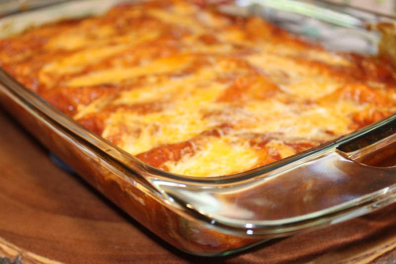 baked enchiladas in a glass casserole dish