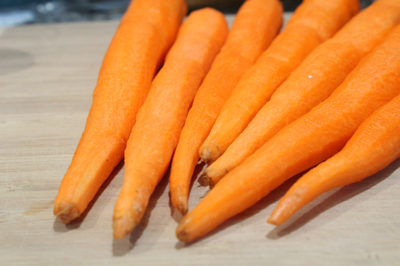 peeled carrots sitting on a cutting board