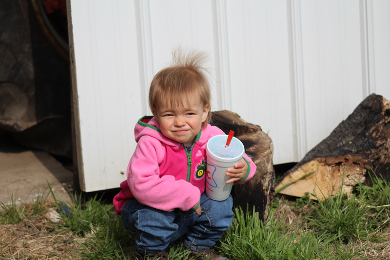 little girl squatting in front of a barn holding a slushy wearing a pink jacket with a tractor on it