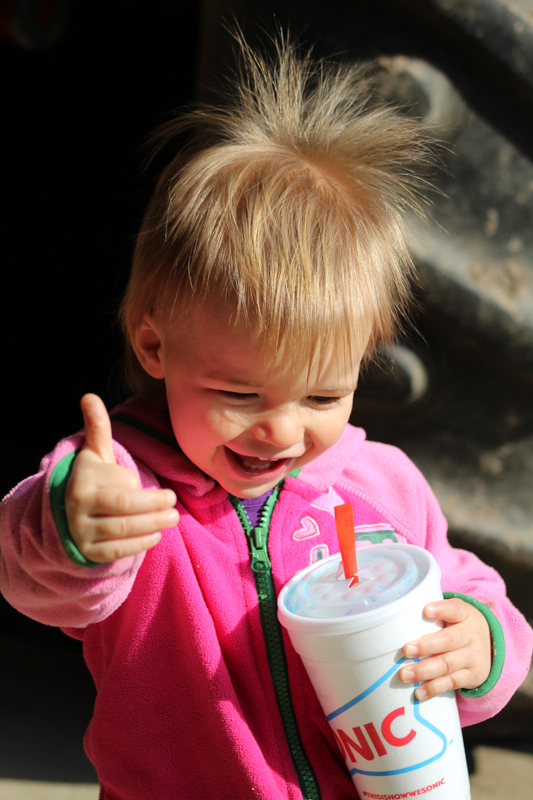 little girl giving a thumbs up while holding a sonic cup