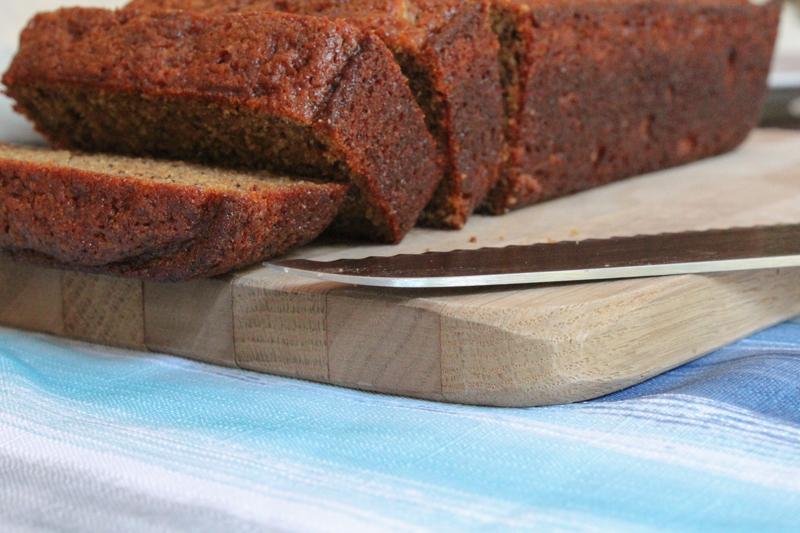 sliced einkorn banana bread on a cutting board with a knife