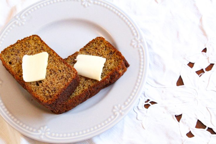 two slices of einkorn banana bread topped with a pad of butter sitting on a light blue plate with a white table cloth