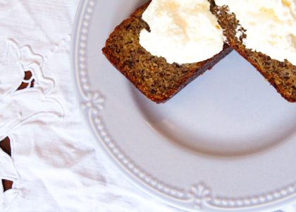 two slices of einkorn banana bread topped with whipped cream on a light blue plate sitting on a white table cloth
