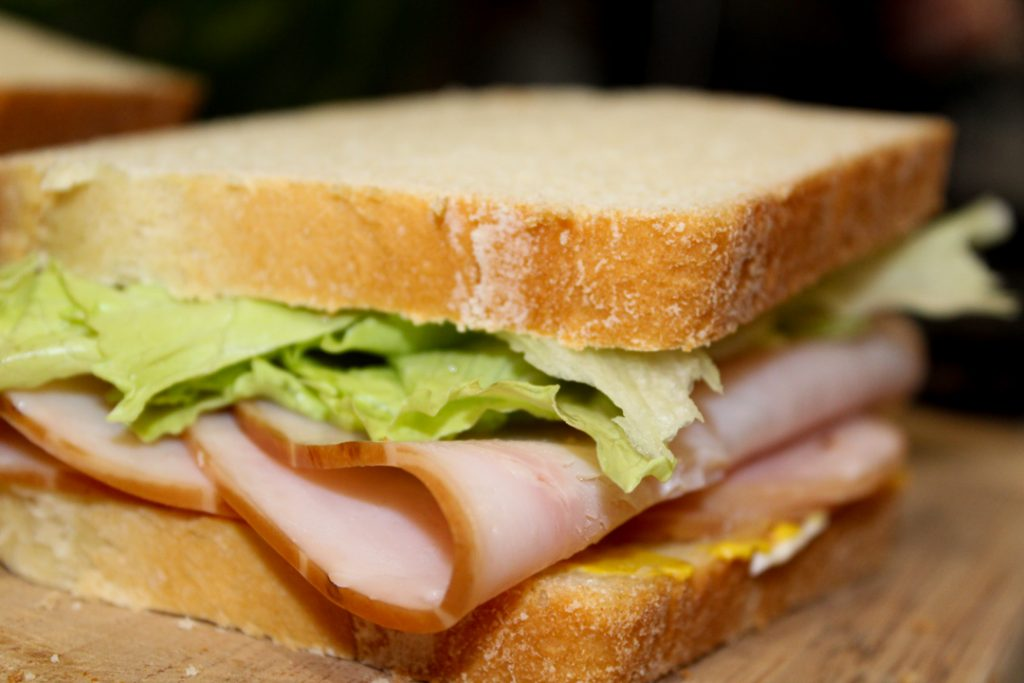 A roasted turkey sandwich on homemade bread. It has the top slice of bread followed by crisp green lettuce, two slices of turkey, and mayonnaise and mustard spread on the bottom slice of bread. The sandwich is sitting on a cutting board.