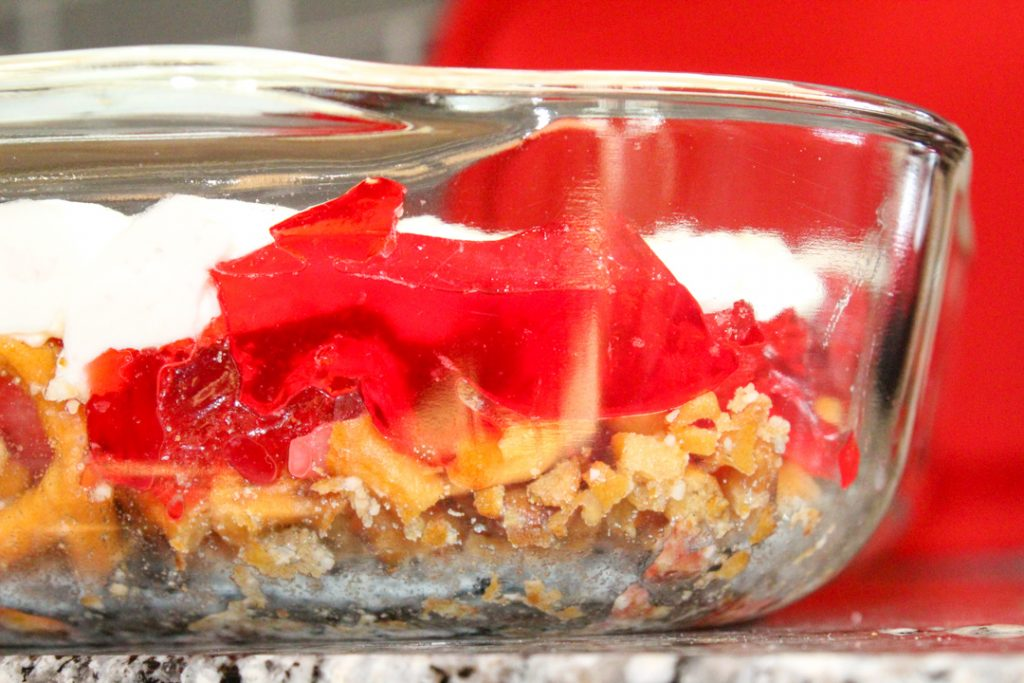strawberry pretzel salad in a glass dish. It is a side view where you see the pretzels, then the fruit filled jello, and lastly the white whip cream/cream cheese topping.