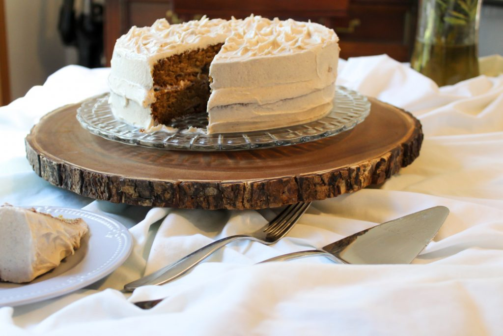gluten free apple spice cake with a slice missing sitting on a crystal platter on a round wooden slice. There is a white table cloth on the table. In the foreground is a cake server, a fork, and a light blue cake plate with a slice of cake on it.