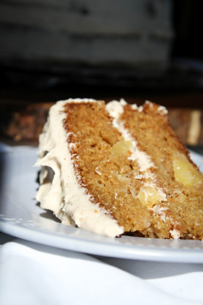 One slice of gluten free apple spice cake sitting on a light blue round plate. There is a white table cloth in the foreground and the background is nearly black, but you can see the cake sitting behind it.