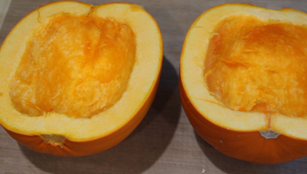 A pumpkin cut in half with the seeds scooped out. They are sitting on a cutting board.