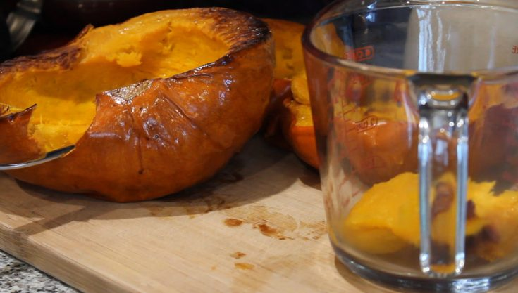 roasted pumpkin on a cutting board with a spoon in it. Glass measuring cup sitting to the right of it with roasted pumpkin chunks in it