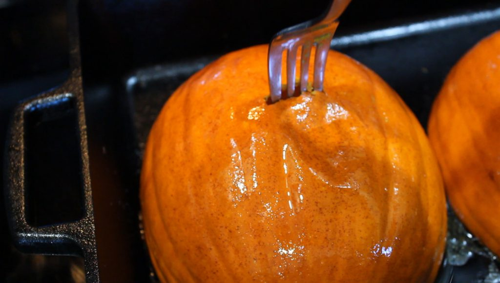 roasted pumpkin halves siting skin side up in a 9x13 cast-iron pan. Fork is piecing the pumpkin to test if it is tender.