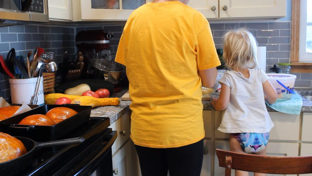 Roasted pumpkins sitting in pans on the stove top on the left. Mother and daughter scooping out roasted pumpkin at the counter. Little girl is standing on a chair to help her mom.
